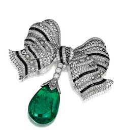 ONYX, EMERALD AND DIAMOND BROOCH.  Designed as a bow, set with single-, circular-, rose- and brilliant-cut diamonds and calibré-cut onyx, suspending an emerald drop,  fitted case.