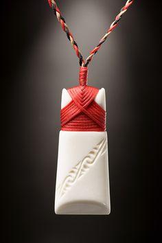 Toki Knochen Symbol Schmuck Anhänger mit roter Bindung in kleiner Ausführung       . • Gearbeitet aus Rinderknochen   • Traditionelle Bindung   • Verziert mit einer Gravur   • Inklusive geflochtener und...
