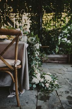 A billowing vine of flowers cascades off of a rustic dinner table.