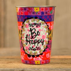 "Durable and easily stackable cups are a generous 17oz and features ""Be happy"" on colorful background."