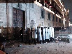 encapuchado atras de los granaderos oculto despues de haber incendiado la puerta del palacio nacional