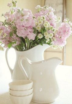 Soft pink and off-white, slightly yellow flowers in a white pitcher.