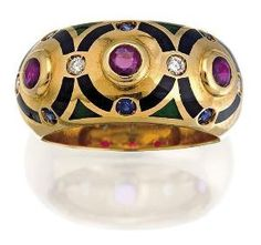 Ruby, sapphire, onyx, enamel and diamond ring, Cartier, circa 1994, of hoop design set to the centre with three circular-cut rubies within a buff onyx surround highlighted at intervals with similarly cut sapphires and diamonds, with enamel accents, mounted in 18ct gold, numbered C 94408, size 55/O, signed Cartier. by judy