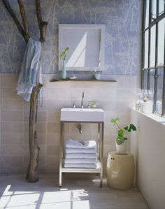 In the bathroom, a large tree limb doubles as a towel rack. A plank of weathered driftwood, mounted to the wall above the sink, serves as a bathroom shelf. Underfoot, small stone mats are taped together to create a massaging bath mat. (Martha Stewart Living)