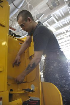 GULF OF OMAN (June 17, 2013) Aviation Ordnanceman 3rd Class Joseph R. Wilkinson from Bremerton, Wash., performs maintenance on an R-14 forklift in the hangar bay of aircraft carrier USS Nimitz (CVN 68). Nimitz Strike Group is deployed to the U.S. 5th Fleet area of responsibility conducting maritime security operations, theater security cooperation efforts and support missions for Operation Enduring Freedom. (U.S. Navy photo by Victoria I. Ochoa/ Released)