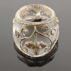 A Mughal style rock crystal archer's ring, 20th century. Gold inset and jewel embellished with floral designs.