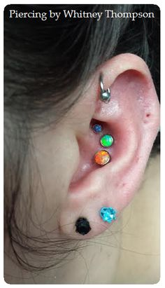 Triple Conch with ascending opals; purple, lime and orange. Jewelry from ANATOMETAL.Reminds me of skittles.