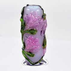 Lampwork glass flower focal bead made with Bullseye glass, lilac base bead with soft transparent lilac flowers and sparkling adventurine green leaves and stems.  Bead stand not included.  Bead measurements are approx Bead hole approx 2.5mm Bead measures approx 35mm top to bottom x 15mm across  THE SMALL PRINT.....  Each bead is made on 3/32 sized mandrels which gives approx. 2.5mm beading hole.  Each of my beads come from my imagination inspired by the world around me and are handmade.  ...