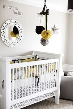 I love several things about this picture: The coffee filter balls (poofs) hanging like a mobile and what looks like a re purposed white mirror with the words you are my sunshine and then the striking color choice/theme of the whole nursery. Brilliance!