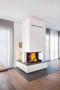 Der Dreiseiter mit 80 cm Scheibenfrontbreite ist vor dem Schornstein montiert. Dadurch liessen sich rechts und links hinter der Feuerung Holzfaecher realisieren. Bodenbelag und Sockelabdeckung sind aus Grauwacke hergestellt.