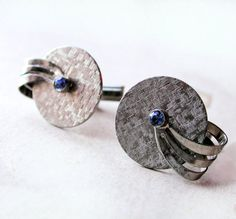 These are handsome modernist 1950s cufflinks, they are textured round silver tone discs with a small sapphire blue rhinestone in the center of each,