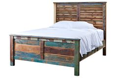 Reclaimed Wood Bed queen platform bed crafted from reclaimed sheesham and teak. a stripped finish for a distinctive appeal and slanted panels with a low footboard.