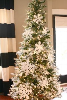 Flocked tree with snowflake ornaments.  ~ 20 Awesome #ChristmasTree Decorating Ideas & Inspirations - Style Estate -