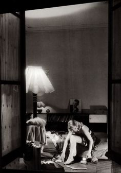 A young girl sitting on her bed, seen through her open window, Paris, 1946  by Willy Ronis