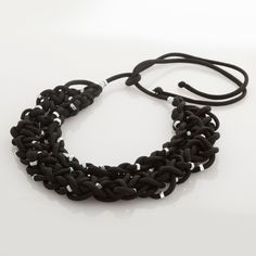 """""""Intreccio nero con dadi"""" is an handmade necklace, made of cotton cable and nylon with metal's elements, plaited with fingers.This optional count on the light effect of metal's nut. 100% made in Italy. Weight: 116 gr. Color: black."""