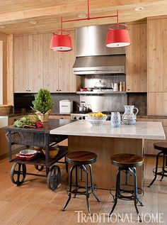 Trip Haenisch.Shown: Rustic knotty-alder cabinetry warms the feel of a marble-topped island built around a vintage French factory cart. Vintage-inspired draftsman's stools pair industrial steel with rugged wood seats. A double-pendant light from The Urban Electric Co. lends a splash of red