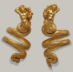 ignudiamore:  Armbands. Gold. Hellenistic Greek, 200 BC. These serpentine armbands represent two tritons, male and female, each holding a small winged Eros. The hoops behind the tritons' heads were used to attach the armbands to the sleeves of a garment, for otherwise their weight (each over 61/2 ounces) would have caused them to slip down the arms.
