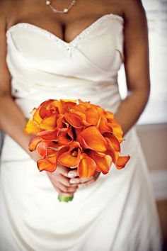 The bride chose vibrant orange calla lilies for a stylish bouquet.    Love it? Get It!Kelley's Bloom Room