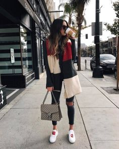 A thick scarf layered over a coat, destroyed jeans, and embroidered sneakers.