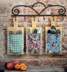Tábuas de cozinha com bolsinhos de pano viram porta-talheres úteis e decorativos. Para prender o tecido, você pode usar grampeadores para madeira e fazer o acabamento com sianinha