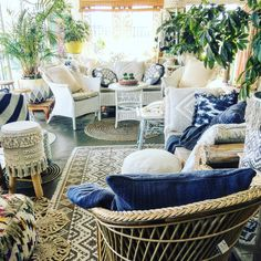 Lovely cane furniture mixed with blue and white cushions .