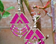 These are handmade beaded earrings I made that are inspired from the Native American peyote stitch. They feature a beautiful rainbow red pink
