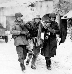 A wounded American medic is helped to an aid station during the Battle of the Bulge