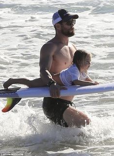 I've got you: Very much the hands-on father, Chris carried the surfboard in both hands, allowing his son to lay on top