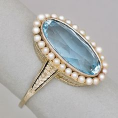 14K WHITE GOLD AQUAMARINE AND SEED PEARL RING. Elongated oval faceted aquamarine, 4.2 cts. by formula, in millegrained bezel setting, surrounded by a halo of post set seed pearls, engraved gallery and shoulders, ca. 1930.