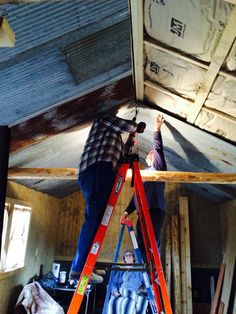 James and Bobby hanging the reclaimed tin ceiling.  They just measured the tin used the hot saw to cut and it is screwed up with galvanized screws to the 2x4 in the ceiling.  Did the entire cabin in 1 day.