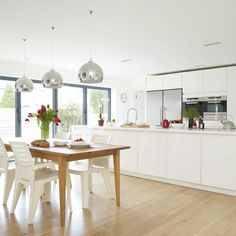 Bright airy kichen. Love the low hanging lights over the dining table