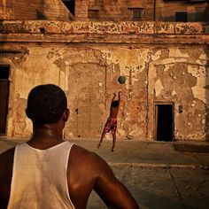 A Cuban man and boy play basketball in Havana. This street the Malecon is popular among tourists for its classic cars and beautiful crumbling sea front architecture. But it is also some of the most valuable real estate and highly sought after as the country braces for an influx of new visitors. @natgeo by dguttenfelder