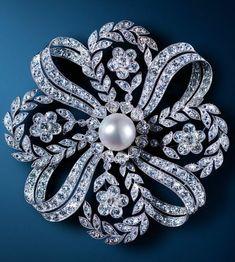 An Edwardian diamond and pearl ribbon brooch.