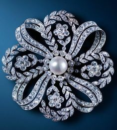 An Edwardian diamond and pearl ribbon brooch.