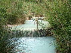Le acque temali a Bagni San Filippo hanno creato un paesaggio magico di bianche formazioni calcaree, cascatelle e piccole vasche di acqua calda nel mezzo di un verde bosco rigoglioso