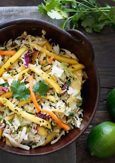 Light, fresh and crisp slaw made with shredded cabbage, carrots, lime juice, rice vinegar and a slightly under-ripe mango topped with sesame seeds.