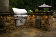 An outdoor kitchen with lighting, a grill , outdoor refrigerator and counter-top improves the outdoor cooking and dining experience. Place this set-up inside of a loggia and put a bar counter and bar stools overlooking a cascading waterfall pool, and sheer perfection awaits you!