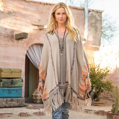 "PAUMA FRINGED PONCHO -- Spread your wings in this classic fringed cotton poncho adorned with bold tribal patterns, front and back. Flowing macramé fringe makes this a forever classic. Cotton. Machine wash. Imported. One size fits most adults. Approx. 35-1/2""L at longest point."