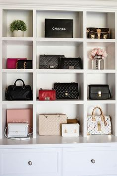 In a small closet alcove, designer bags sits in built in purse shelves positioned above white drawers donning polished nickel knobs.