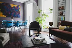 There are very few colors that work in monochromatic rooms but, surprisingly, purple is one of them. Two rugs and the dining room walls compliment the dark mahogany of the floor, the gold accents, and teal dining chairs. You can be bold with your color choices as long as you think carefully about how well they work in your space — and how likely it is that you'll get sick of them (so no neons!).
