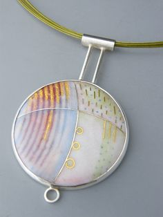 Ruth Ball - Materials: Enamel /  Silver / Gold Foil - available with a silver or coloured cable neckband.Size: Pendant 42mm diameter  Techniques: Cloisonne and enamel painting. Price : with silver neckband £395 -  with coloured clable neckband £350 Availble to Order  STATEMENT  The pendants are enamelled in shades of white, tinged with pale blues, icy greens and subtle hints of earth brown, and are highlighted with flashes of gold foil.