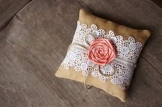 A simple square pillow of brown burlap material is stuffed with polyfill stuffing, completed with lace and rose over on top and tied with twig.