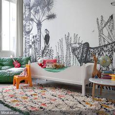 Das Kinderzimmer wird von einer Wandtapete mit Dschungel-Motiv in den Farben Schwarz und Weiß dominiert. Der gemusterte Teppich, das Sofa in Grün und der gelbe …