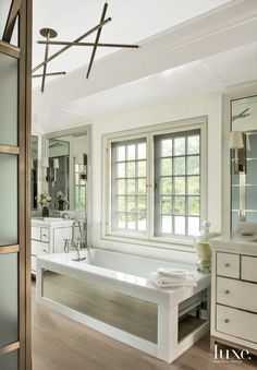 Modern White Master Bathroom with Mirror-Paneled Tub