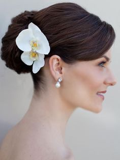 The bride will have a single gold orchid bloom pinned in her hair.