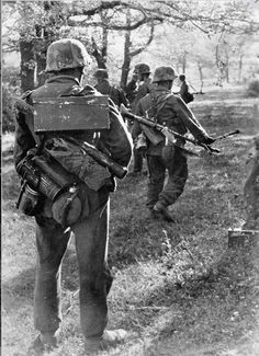 "kruegerwaffen: ""Infantrymen in the Donets basin in the southern sector of the Eastern front. On the right is an MG gunner with an MG 34. The soldier in the foreground is carrying a munitions case on his back, as well as spare barrel."""