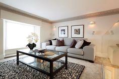 Beige walls, grey sofa, with warm purple cushions / colour