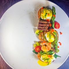 Eggs benedict with quail eggs, steak, shrimp, wilted spinach asparagus and a salad of grape tomatoes and cucumbers.