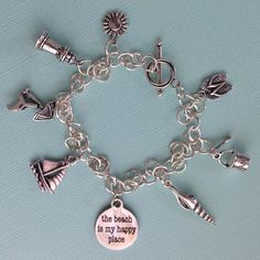 Beach Lovers Charm Bracelet  This silver finish charm bracelet makes a perfect indulgence or gift for beach and summer enthusiasts.  Charms have been worn since ancient times. At first they were carried to ward off evil spirits or to bring good luck. Queen Victoria created the modern day charm bracelet fad of wearing charms as decorative jewelry in the late 1880s. Today charms are worn to share the personal life stories of the owner.  * Complimentary gift box included.  Charms include…