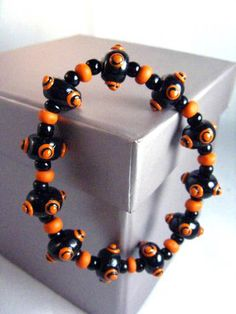 Black and orange polymer clay beads make up this stretch bracelet. This funky…
